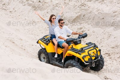 high angle view of happy young couple riding ATV in desert