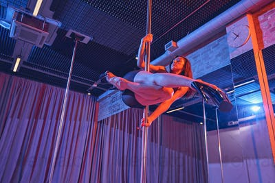 Beautiful young lady dancing on pylon in nightclub