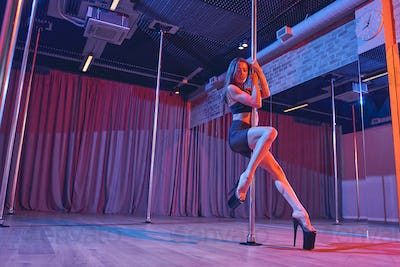 Sexy young woman doing pole dance trick in nightclub