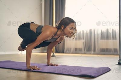 Joyful young woman practicing yoga in studio