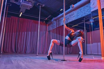 Beautiful female dancer doing pole dance trick in nightclub