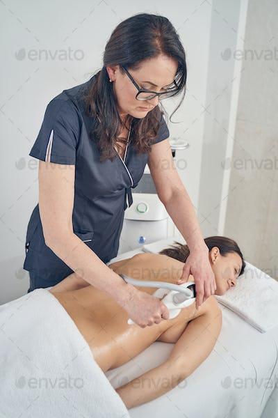 Careful beautician using non-invasive body contouring method