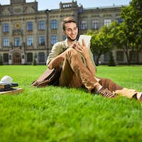 Joyous male student sitting on the grass