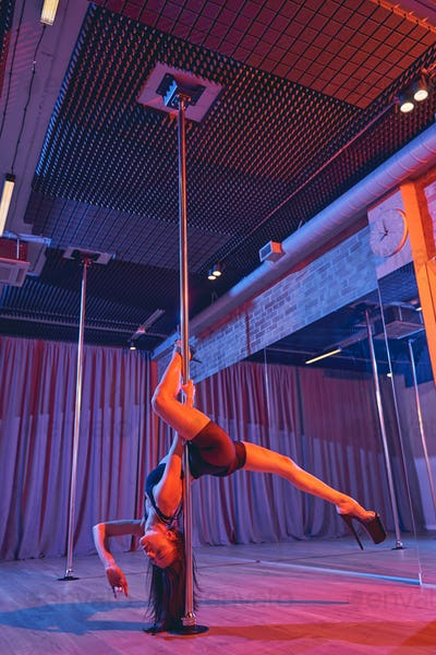 Sexy female dancer performing in pole dance studio
