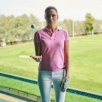 Serene female golfer standing in front of the camera