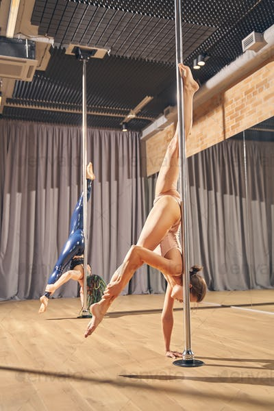 Beautiful young women demonstrating pole dance skills