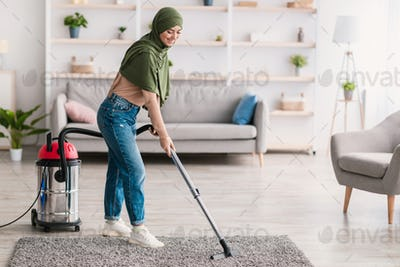Low section of woman cleaning carpet with vacuum cleaner