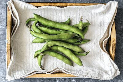 Fresh organic broad beans in a wooden box aerial view