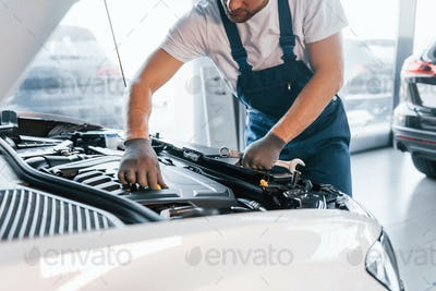 Quality service. Young man in white shirt and blue uniform repairs automobile