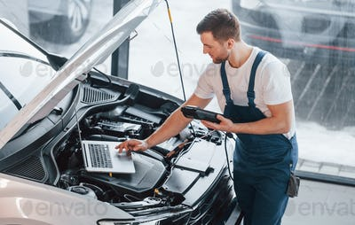 Uses laptop. Young man in white shirt and blue uniform repairs automobile