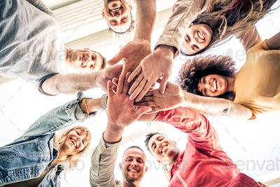 Young happy people stacking hands together outcoor