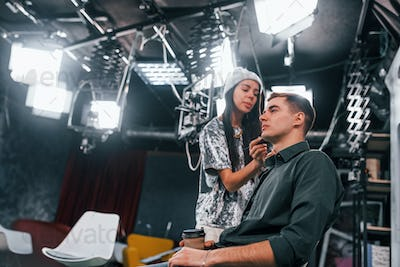 Young man is preparing for TV online broadcast. Woman helps with make up