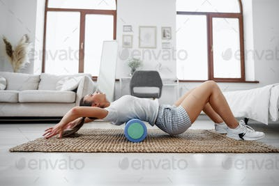 Young woman doing exercise with gymnastic roll on the floor at home