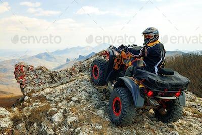 Man in helmet sitting on ATV quad bike in mountains