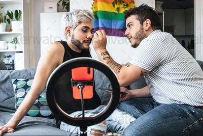 Drag queen and gay man streaming online make up tutorial with mobile phone camera indoors at home