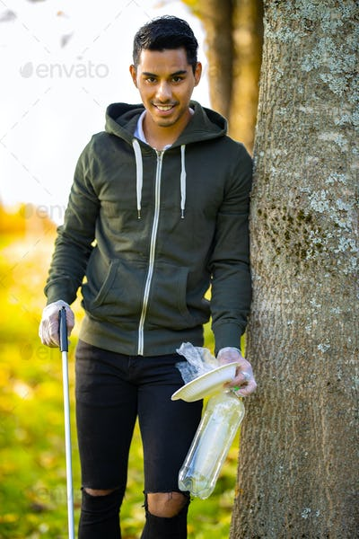 Smiling environmental protection volunteer holding garbage and mechanical grabber