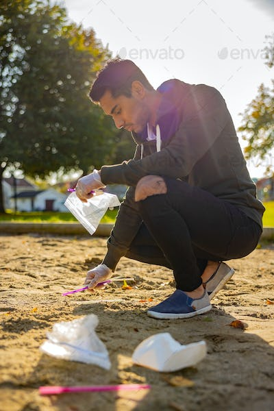 Back lit of male volunteer cleaning garbage on sand at park