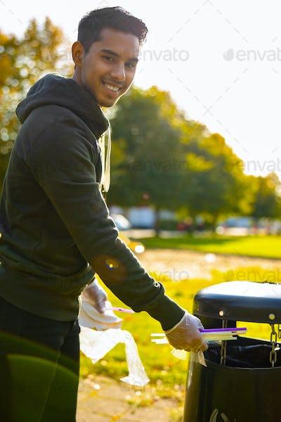 Smiling young man putting straws in garbage bin at park