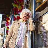 Tired old age female wearing coat with multicolor shopping bags