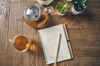 Notebook with female face sketch and tea on wooden table