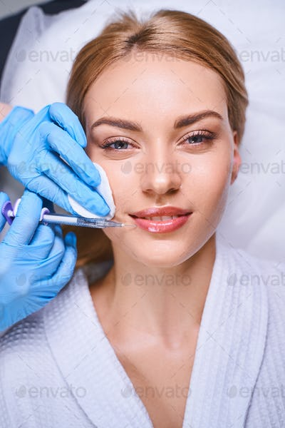 Happy woman during beauty injections stock photo