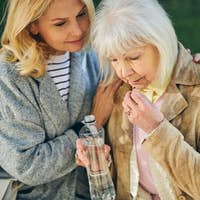 Elderly woman drinking water while another female sitting near her