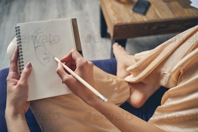 Young lady drawing in notebook at home