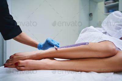 Woman doing waxing in salon stock photo