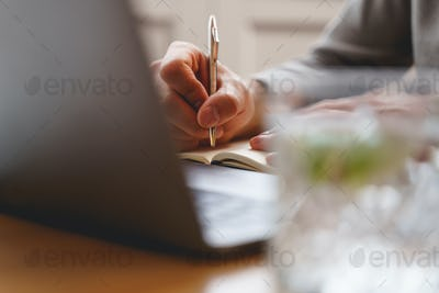 Young man writing in notebook in cafe