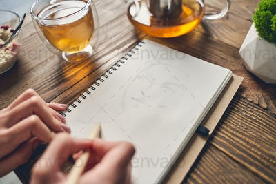 Female artist drawing sketch in notebook at home