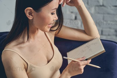 Cheerful young woman drawing in notebook at home