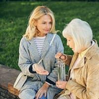 Mature lady feeling ill near female friend in the park