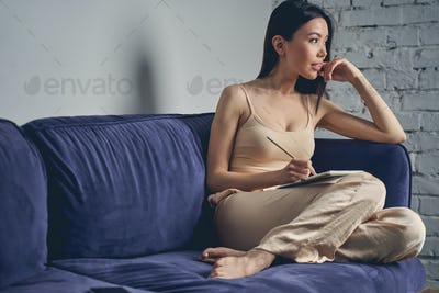 Beautiful young woman sitting on sofa at home