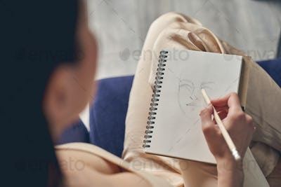 Young woman drawing in notebook at home