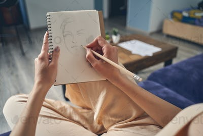 Talented female artist drawing in notebook at home