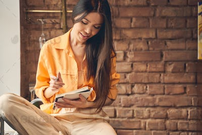 Beautiful young woman holding spiral notebook and smiling