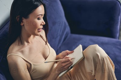Charming young woman writing in notebook at home