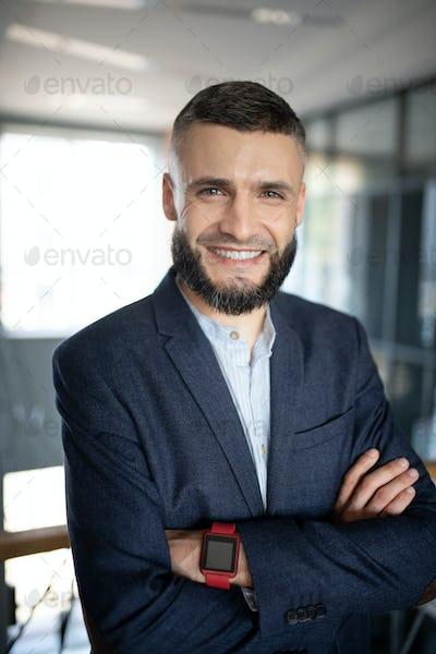 Bearded businessman smiling broadly while feeling good
