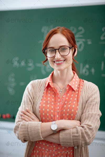 Stylish experienced teacher wearing glasses smiling