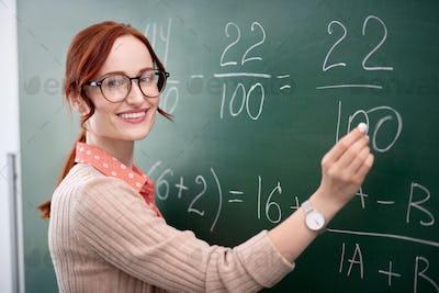 Experienced math teacher standing near blackboard with chalk