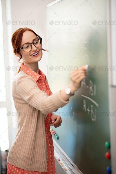 Teacher wearing hand watch writing on blackboard