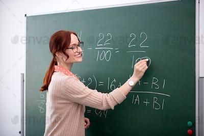 Smiling math teacher explaining new topic to her pupils