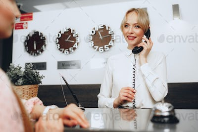 Female receptionist in hotel talking on the phone at work