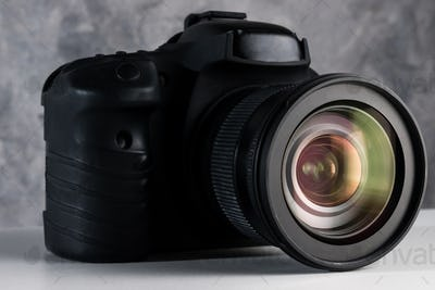 Black digital camera on a table with grunge background.