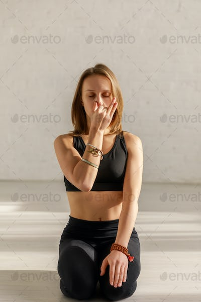 woman with closed eyes doing breathing exercise while sitting on floor