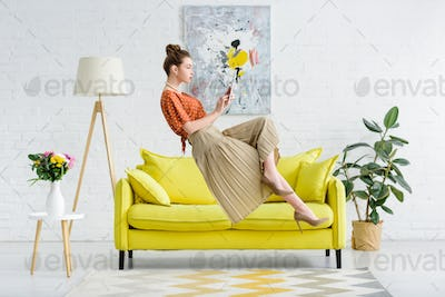 elegant young woman levitating in air and using digital tablet in living room