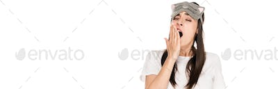 brunette young woman in cat sleeping eye mask yawing isolated on white, panoramic shot