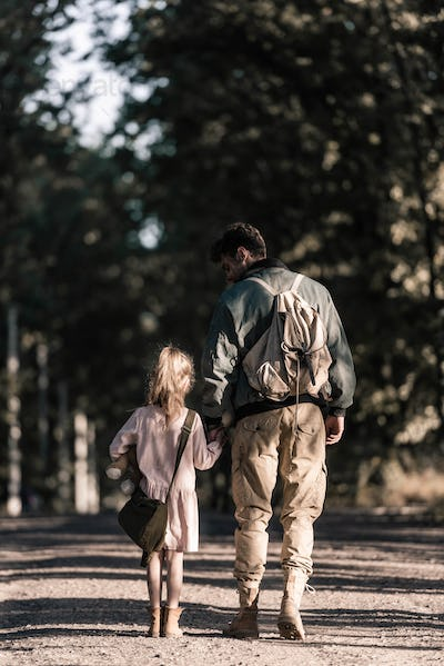 back view of kid holding hands with man while standing on road, post apocalyptic concept