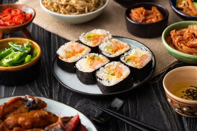 selective focus of gimbap with salmon near chopsticks and korean side dishes