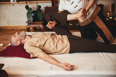 Joyful grizzled man exercising with manual therapist